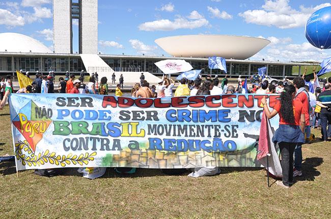 Foto mostra centenas de estudantes em frente ao Congresso Nacional, impedidos de entrar na Casa, com uma faixa nas mãos com os dizeres:  ser adolescente não pode ser crime