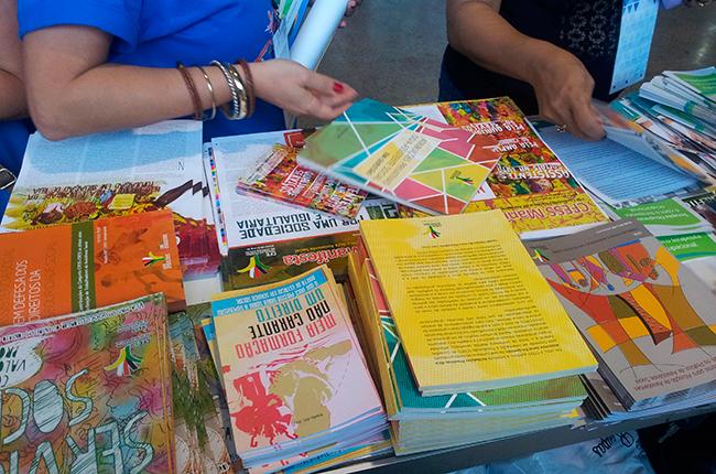 Imagem mostra estande com diversos livros e brochuras distribuídos pelo CFESS