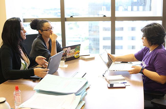 Imagem mostra as 3 integrantes da Comissão Nacional Eleitoral, reunidas em mesa de reunião, em uma sala do CFESS.