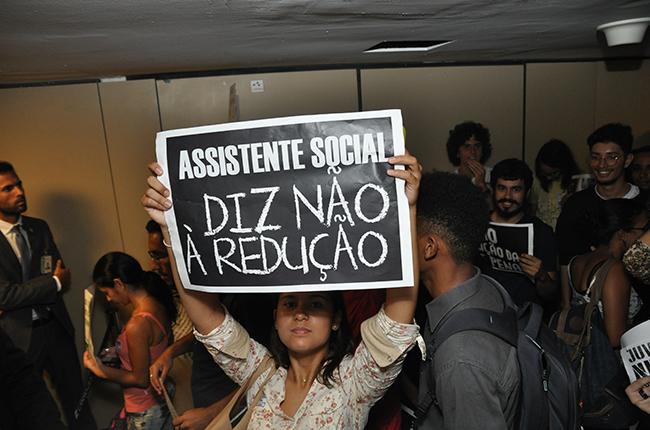 Foto mostra mulher segurando cartaz com os dizeres Assistente Social diz não à redução