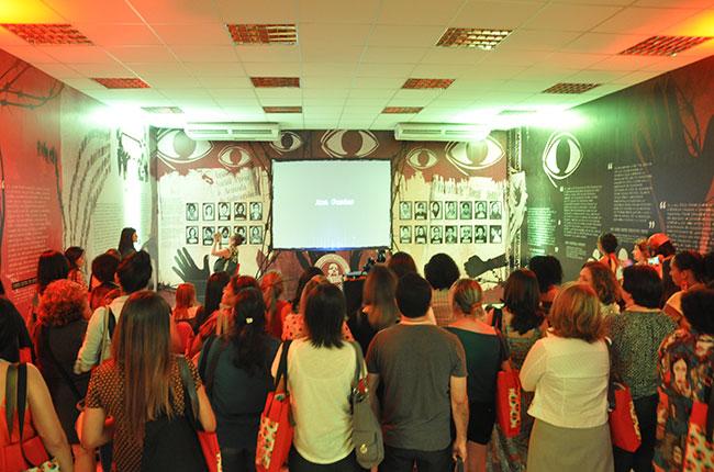 Imagem do público assistindo ao vídeo produzido para a exposição