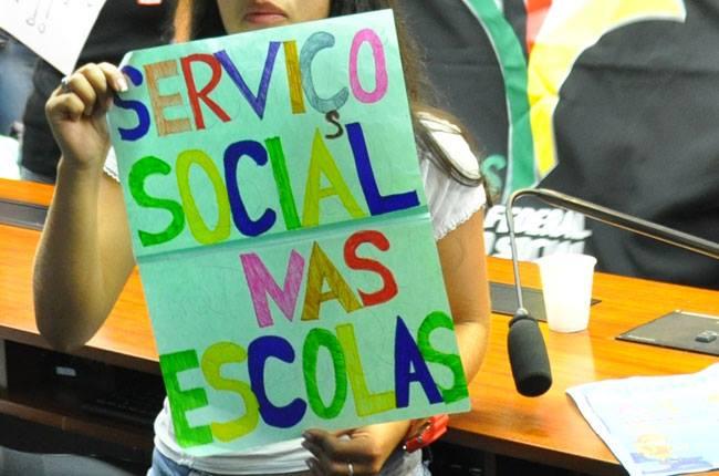 Imagem de uma estudante com o cartaz com os dizeres Serviço Social nas Escolas