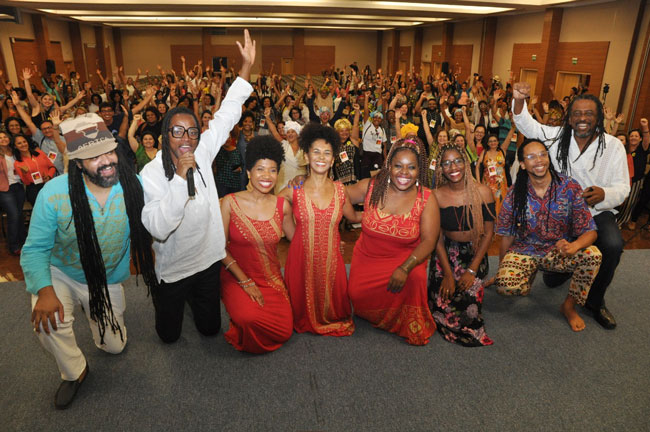 Imagem de cima do palco, com o grupo da atividade cultural à frente, e o público ao fundo, todos com as mãos levantadas.